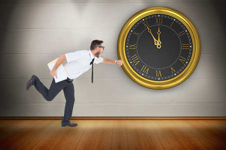 running late: Geeky young businessman running late against room with wooden floor Stock Photo