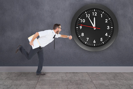 running late: Geeky young businessman running late against grey room Stock Photo