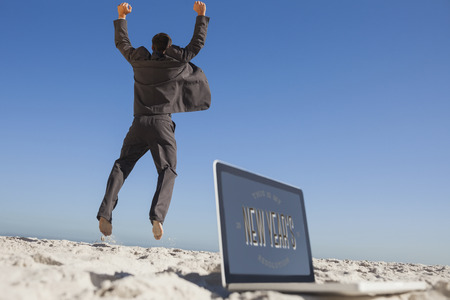 new years resolution: Victorious businessman jumping leaving his laptop against new years resolution