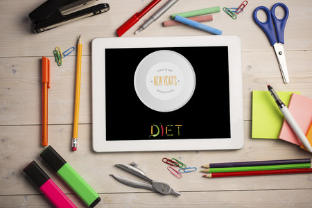 new years resolution: Diet new years resolution against students desk with tablet pc Stock Photo