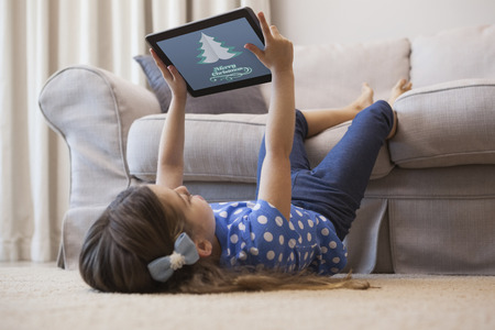 using tablet: Little girl using digital tablet in the living room against merry christmas message Stock Photo