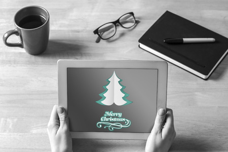 woman tablet pc: Businesswoman holding tablet at desk against merry christmas message