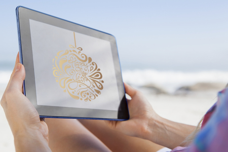 beach happy new year: Woman sitting on beach in deck chair using tablet pc against elegant happy new year