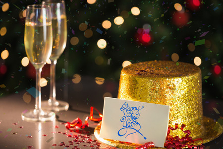 celebratory event: Happy new year card on table set for party with gold hat and champagne Stock Photo