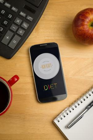 new years resolution: Diet new years resolution against overhead of smartphone with calculator Stock Photo