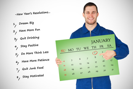 boiler suit: Smiling young mechanic in boiler suit pointing on bcalendar in his hands against green card Stock Photo