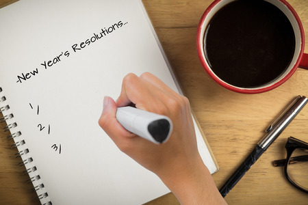 new years resolution: Composite image of new years resolutions against overhead of notepad and pen and coffee Stock Photo