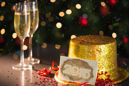 gold flute: 2015 card on table set for party with gold hat and champagne