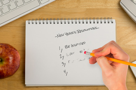 new year's resolutions: Composite image of new years resolutions against overhead of notepad and technology Stock Photo