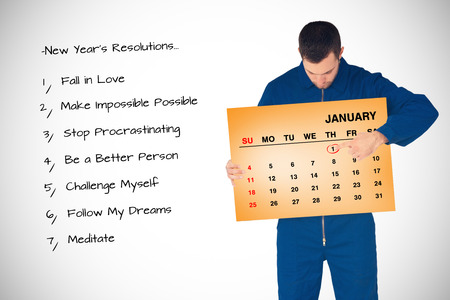 boiler suit: Young mechanic in boiler suit pointing on calendar in his hands against orange card