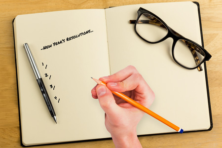Composite image of new years resolutions against overhead of open notebook with pen and glasses