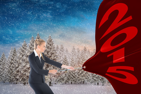 tugging: Focused blonde businesswoman pulling a rope against snowy landscape with fir trees Stock Photo