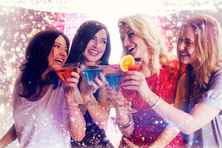 ladies: Friends with drinks against gold and red lights