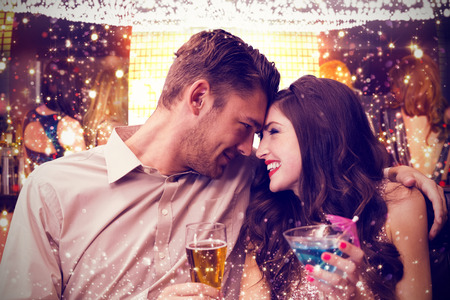 celebrating female: Cute couple drinking against gold and red lights