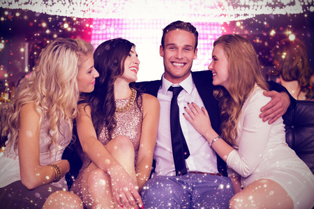 together with long tie: Girls flirting with young man against gold and red lights Stock Photo