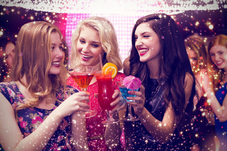 chicas sonriendo: Amigos que beben cócteles contra el oro y las luces rojas Foto de archivo