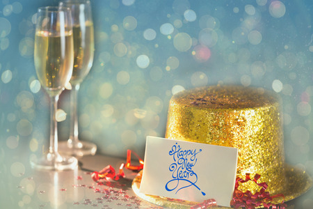 celebratory event: Digital composite of Happy new year card leaning on gold party hat