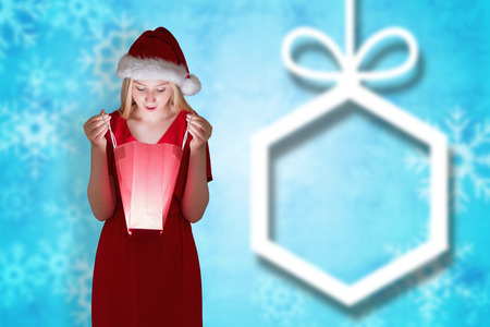 gift bag: Festive blonde opening a gift bag against blurred christmas background Stock Photo
