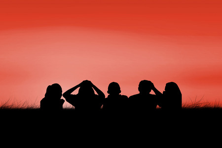 red sky: Silhouettes of football supporters against red sky over grass