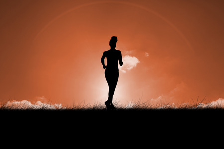 against the sun: Fit brunette jogging away from camera against sun set