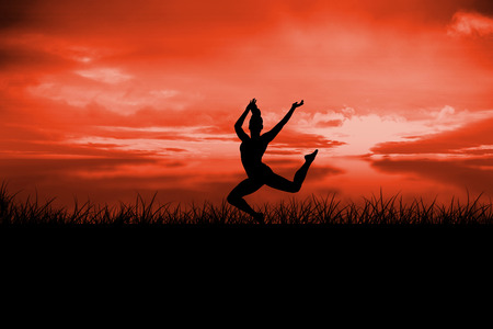 red sky: Fit brunette jumping and posing against red sky over grass