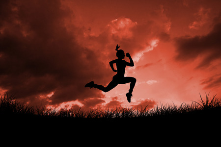red sky: Fit brunette running and jumping against red sky over grass Stock Photo