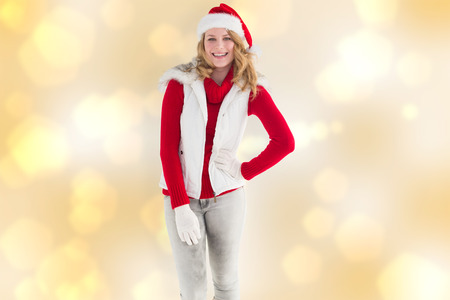 warm clothes: Smiling pretty blonde standing in warm clothes against yellow abstract light spot design Stock Photo