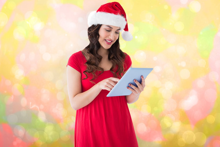 girly: Festive brunette using her tablet pc  against girly pink and yellow pattern Stock Photo