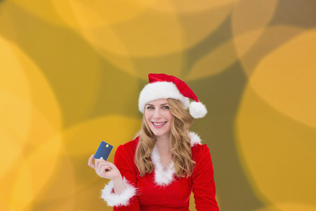 glimmering: Woman with a credit card against blurry yellow christmas light circles