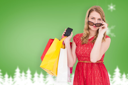 telephoning: Cute woman holding shopping bags and her smartphone against blurred fir tree background