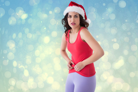 pinching: Festive fit brunette pinching her stomach against blue abstract light spot design