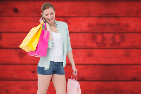 telephoning: Happy blonde holding shopping bags and talking on phone against blurred red planks Stock Photo