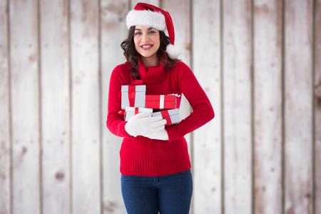 ropa de invierno: Morena festivo en ropa de invierno la celebraci�n de regalos contra tablas de madera borrosas Foto de archivo