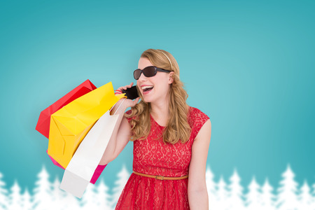 telephoning: Pretty blonde talking on phone holding shopping bags against blurred fir tree background