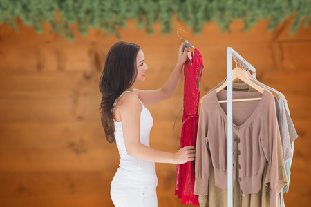 fir  tree: Woman choosing clothes against blurred fir tree branches on wood