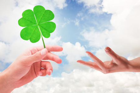 saint patty: Hand showing against blue sky with white clouds Stock Photo