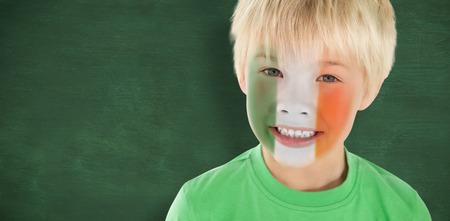 green chalkboard: Cute irish boy against green chalkboard Stock Photo
