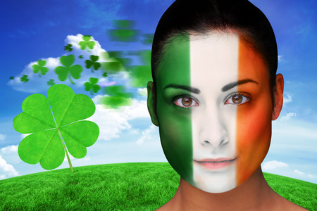 face paint: Brunette in irish face paint against green hill under blue sky
