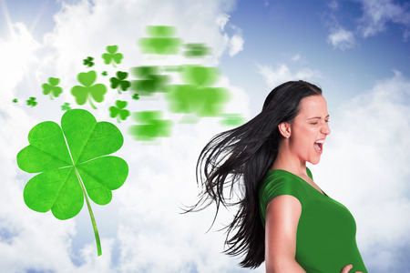 saint patty: Brunette in green tshirt against bright blue sky with clouds Stock Photo