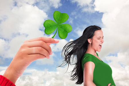 saint patty: Brunette in green tshirt against blue sky with white clouds Stock Photo
