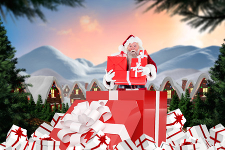 santas village: Santa standing in large gift against cute village in the snow Stock Photo