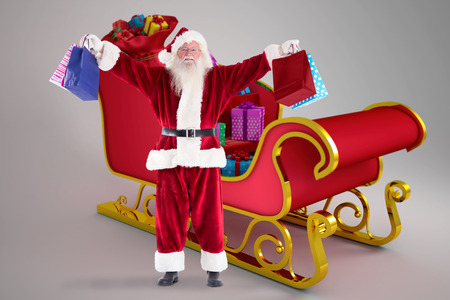 fancy bag: Composite image of santa holds some bags for chistmas against sleigh