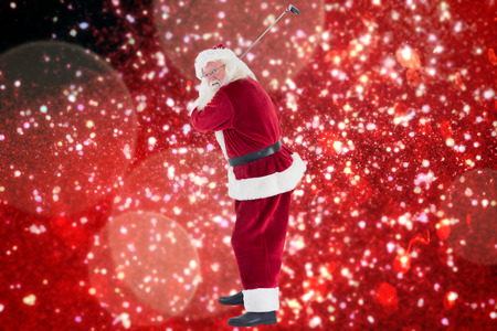 christmas golf: Santa Claus swings his golf club against white snow and stars on red