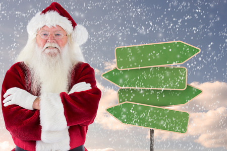 folded arms: Santa smiles with folded arms against empty green road sign Stock Photo