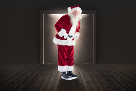 weight room: Santa is surprised about his weight against dark room with opening doors Stock Photo