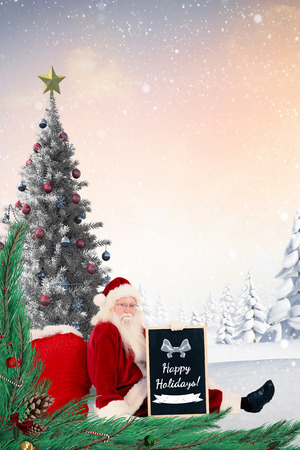 leaned: Santa sits leaned on his bag with a board against christmas tree in snowy landscape