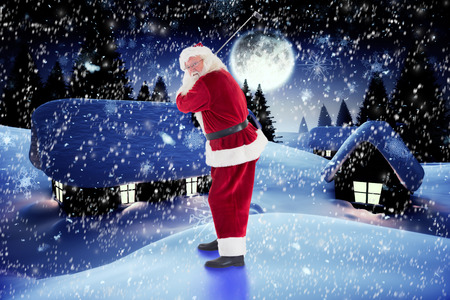 christmas golf: Santa Claus swings his golf club against snow covered village under full moon