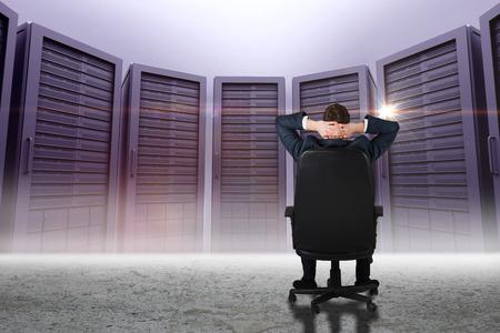 swivel chair: Businessman sitting in swivel chair  against server towers in desert setting