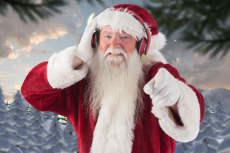 north pole: Santa is listening some music against cute christmas village at north pole