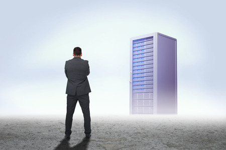 Thinking businessman against server tower in desert setting Stok Fotoğraf